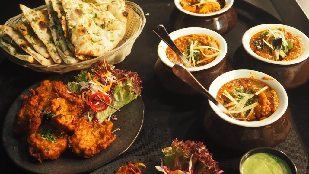 A restaurant spread of food showing a basket of naan, a plate of fritters and bowls of curry.