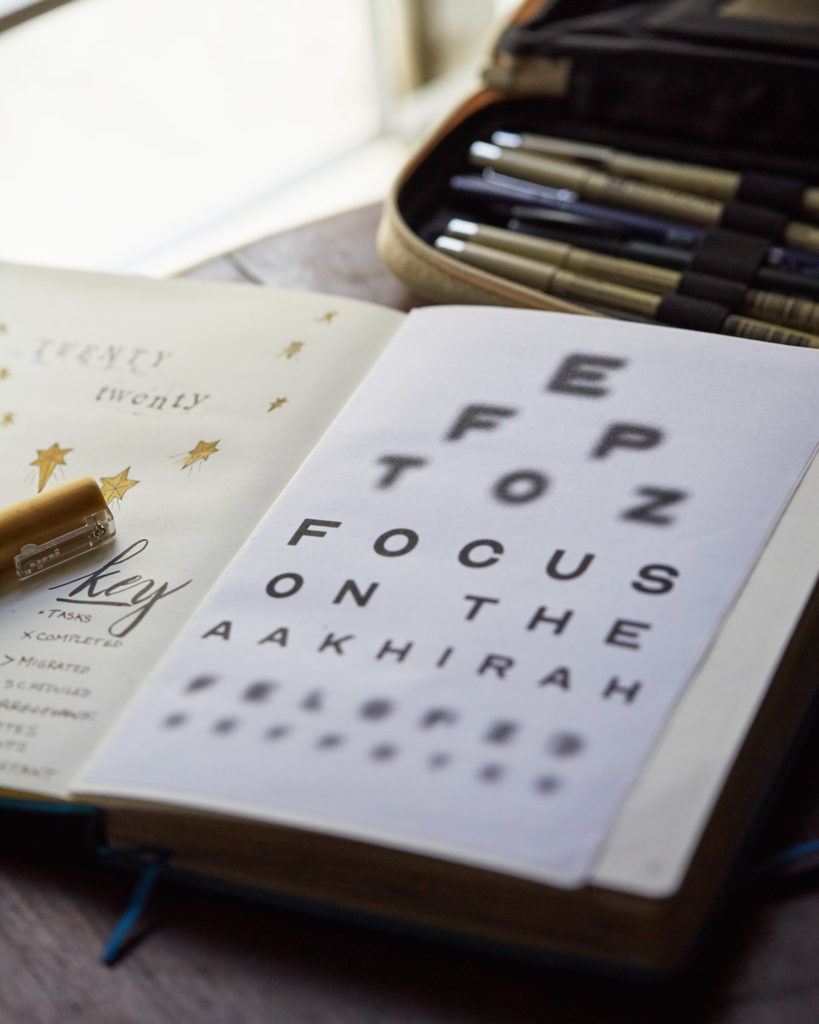 A notebook cover page showing the words Focus on the Aakhirah in an eye chart.
