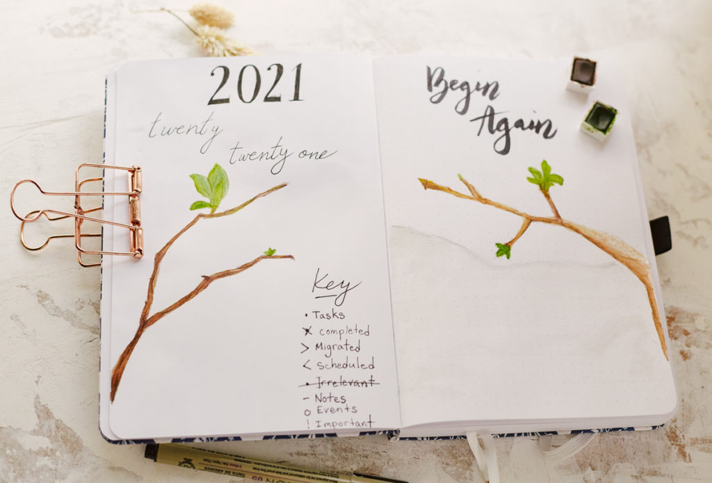 "As explained in the Bullet Journal Guide for Muslim Women, this is a Bullet Journal cover image for 2021 titled ""Begin Again"" and depicting new leaves growing on a branch after winter.."