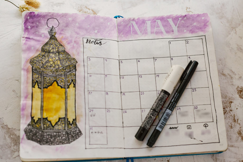 A sample monthly calendar set up for a Bullet Journal depicting the month of May with a glowing lantern, with social media trackers explained in the Bullet Journal Guide.