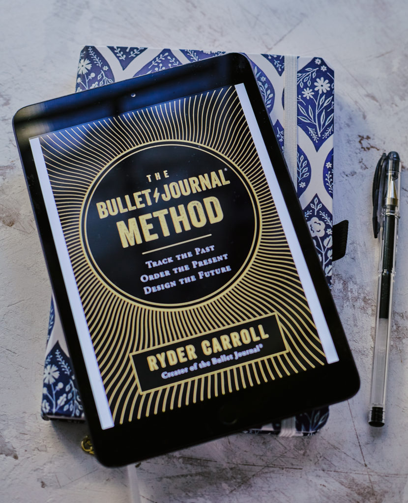 Ebook of the Bullet Journal Method by Ryder Carroll displayed on an iPad on top of a notebook.