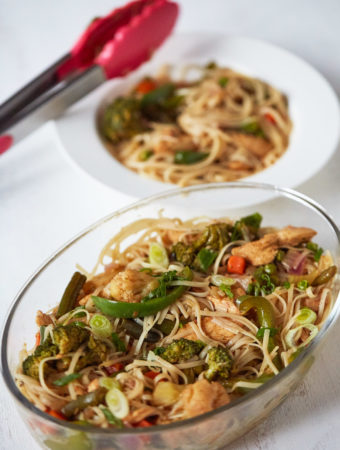 Chicken Stir Fry with Noodles in an oblong glass dish with plated stir fry with noodles in the background