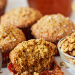 A close up shot of Honey Cornbread Muffins (Makki Muffins) with a giant bite taken out of it to show the texture and walnut chunks inside.