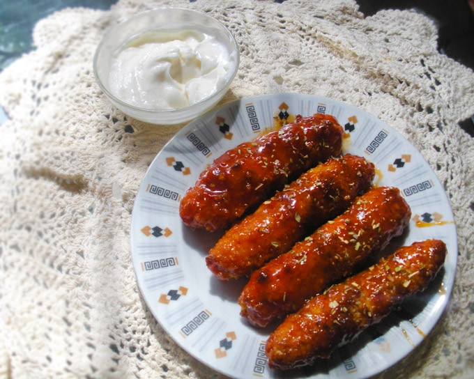 Sweet and Spicy Chicken Sticky Fingers plated on a dish with a garlic mayo dip.