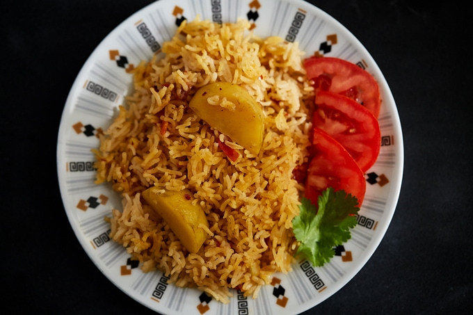 A plate of Tehari (Spiced Rice and Potatoes) with a side of sliced tomatoes, garnished with a coriander leaf.