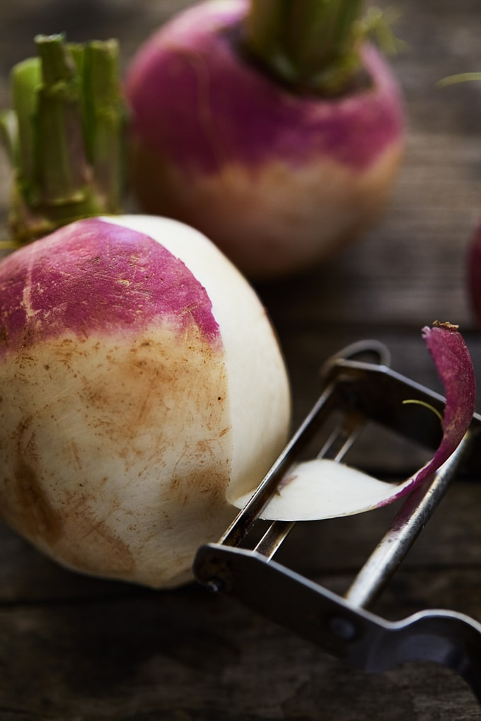 Turnip being peeled by a peeler in preparation for turnip curry (shalgam ki bhujia).