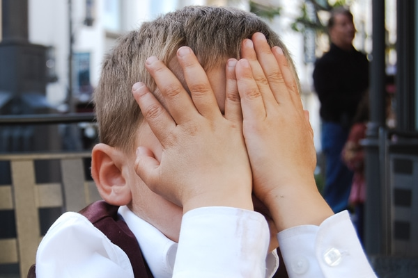 "Child his hiding face with his hands. Used for article ""When Your Child Makes an Inappropriate Joke"""